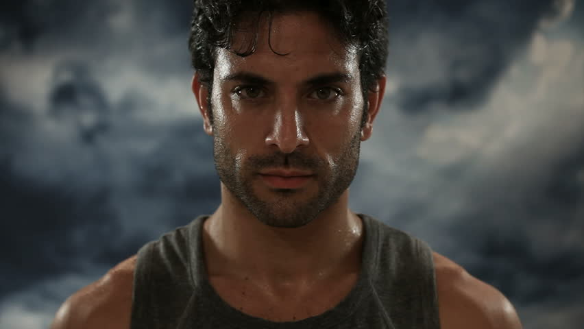 Young exhausted latin man looking at camera during a break of his outdoor jogging training. Portrait of a sweaty man focuses and looking at camera with a storm in the background.