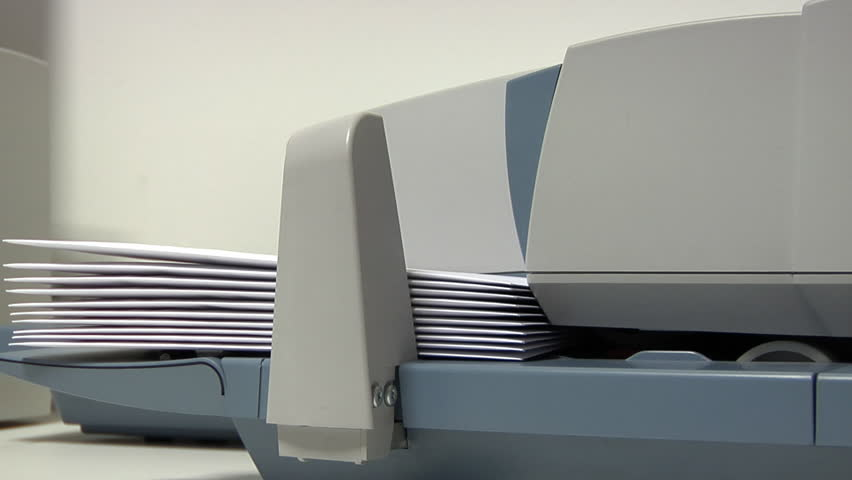 Franking machine pulling in a stack of enveloped letters one by one to apply postage.