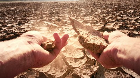 Dramatic point of view slow motion video of climate change concept. Cracked dry land desert and human's hands hold earth dust