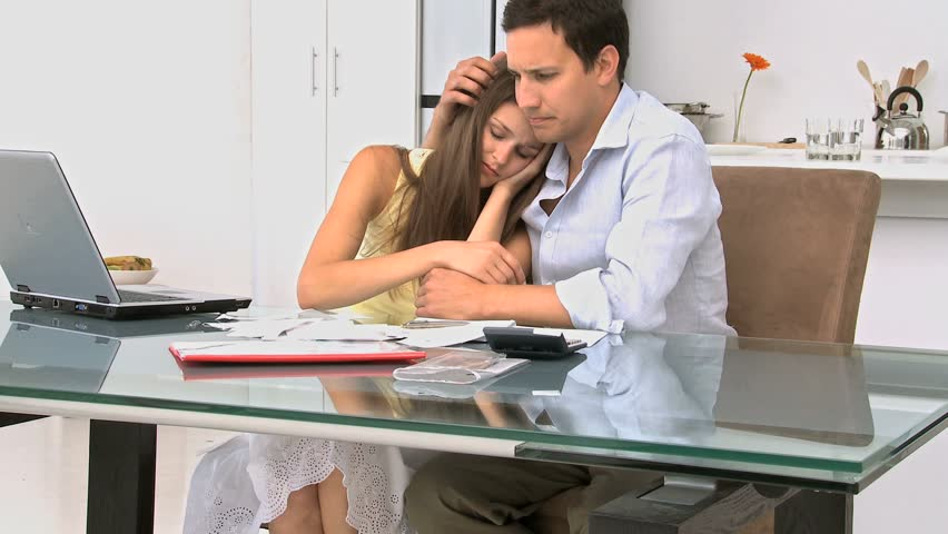 Woman crying in the arms of her husband because of their bills