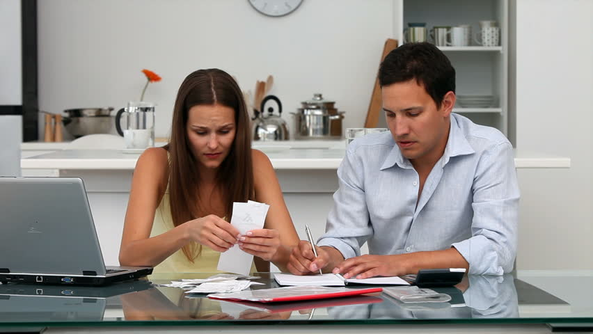 Worried couple paying their bills sitting at a table in the kitchen
