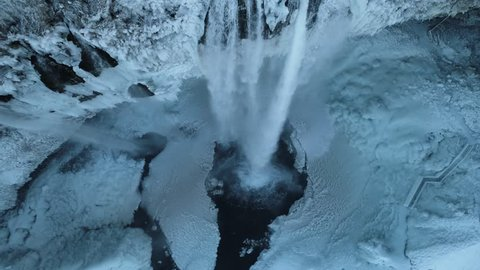 Waterfall View from Above in Winter. Frozen Waterfall Full of Icicles. Arctic Environment. Iceland.