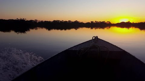 Boat sailing on mirrored river in the Pantanal Biome during twilight. Image in the Pantanal Biome. Mato Grosso do Sul state, Central-Western - Brazil.