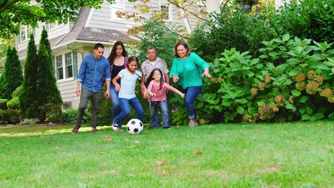 Multi Generation Family Playing Soccer In Garden