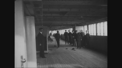 CIRCA - 1919 - President Woodrow Wilson plays shuffleboard with Admiral Cary Grayson aboard the ocean liner George Washington at sea.