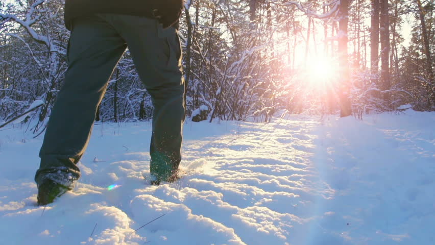 Hiking in the deep snow in winter. Close-up of feet walking in snowy mountain forest on sunset. Winter Journey Adventure. | Shutterstock HD Video #1006650700