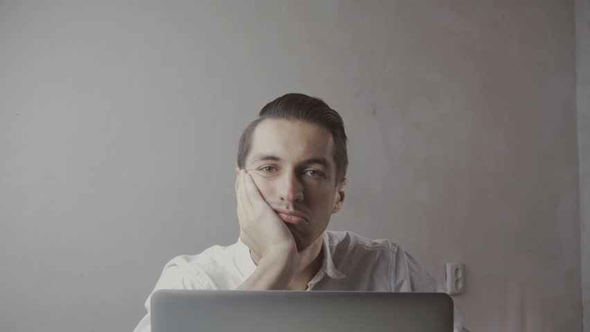Young, bored businessman with laptop sitting by table at Office