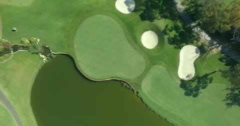 4k aerial of golf green sand bunkers and pond complete with duck family