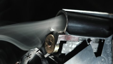 Smoke from the trunks of smooth-bore hunting rifle after firing. Slow motion. Black background.