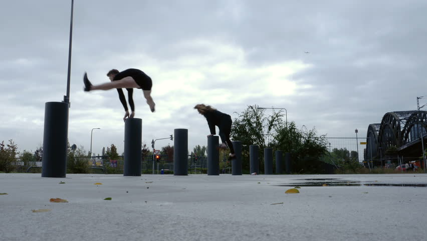 A girl in a suit and a boy in a dress do a pommel jump over bollards. Worm's eye view. Rear view.