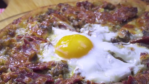 Delicious Turkish and Arabic Traditional Ramadan Food Pide, Lahmacun and Turkish Pizza serving with egg on rotating plate. Round, thin piece of dough topped with minced meat, vegetables and herbs