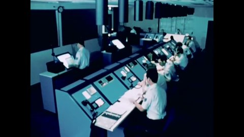 CIRCA 1981 - Air Force technicians work in a control room, and renderings of Defense Satellite Communication System satellites orbiting earth.