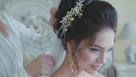 Portrait of young pretty bride while stylist inserting a veil into the brides hair before the wedding in slow motion.