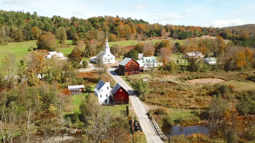 VERMONT - CIRCA 2010s - An aerial over a charming small village scene in Vermont with church, road and farm.