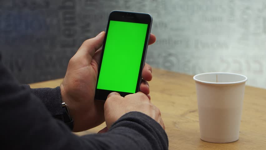 Man using vertical smartphone with green screen. Close-up shot of man's hands with mobile phone. Chroma key. Close up. Vertical | Shutterstock HD Video #1006711090