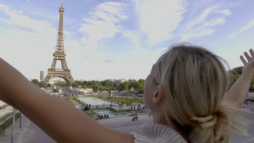 Young woman at Eiffel tower-Paris arms outstretched One blond girl embracing the city of Paris, France. People travel cities concept | Shutterstock HD Video #1006722280