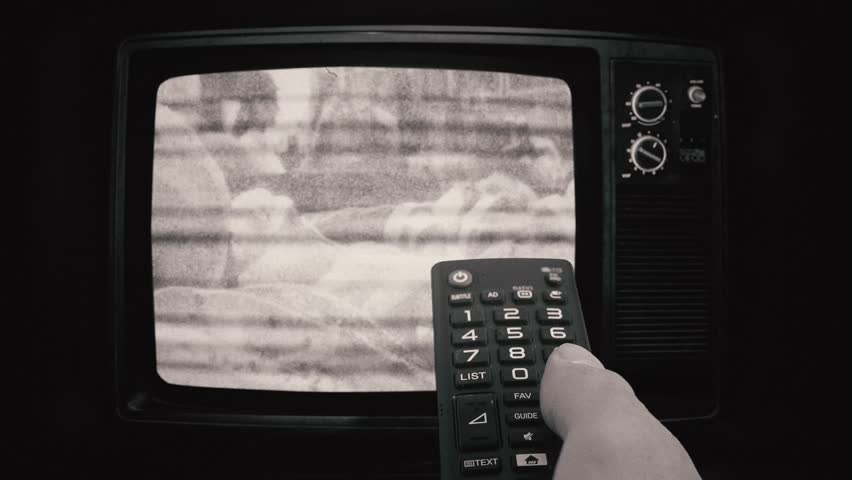 Changing Channels Old Tv Black And White. Male hand using a remote control to change Tv channels on a old television vintage style