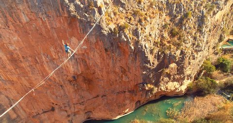 1 Brave Man Slacklining , highlining above a big canyon in Chulilla , Spain . Nature Adventure and leisure sport . Mountain Balance Extreme Hiker Walking Happy, 4k aerial cinematic footage
