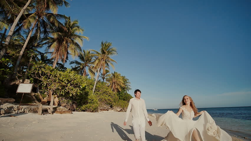 The groom and beautiful bride run barefoot along the sandy shore of the ocean. Happy together. A tropical wedding.