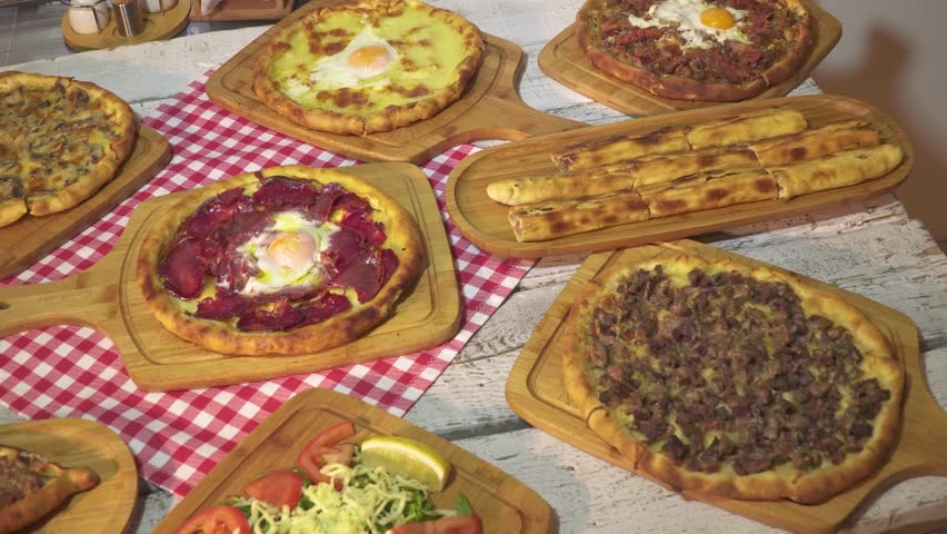 Delicious Turkish and Arabic Traditional Ramadan Food Pide, Lahmacun and Turkish Pizza serving on rustic white wood background. Different kind of Turkish pizzas top view.