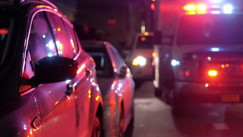 ambulance at accident scene with emergency lights flashing, reflected in car doors.