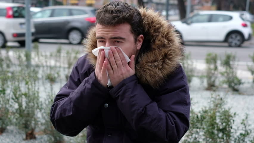 The video is about a sick man sneezing seated on a bench in the city street.The  camera shot slowly moves around the man
