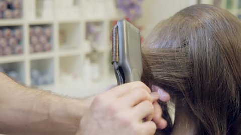 Closeup hairdresser man makes hairstyle for young woman in beauty salon