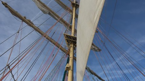 Crew of sailors is working hard setting the square sails on the tall ship
