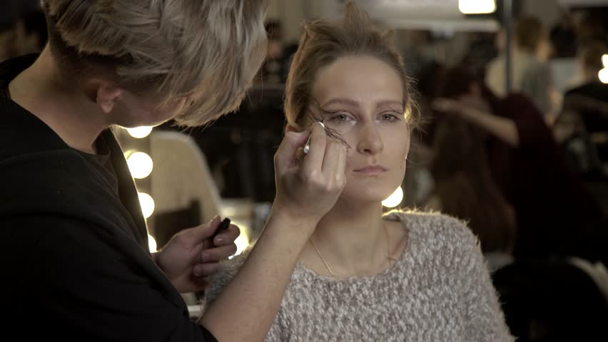 KYIV, UKRAINE - FEBRUARY 8, 2017. Ukrainian Fashion Week. Make-up artist doing make-up for the girl model . Backstage fashion show. | Shutterstock HD Video #1006824130