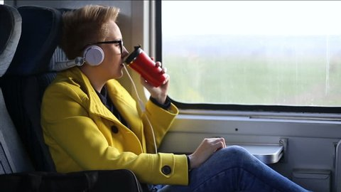Pretty woman listening music in headphones on smartphone riding train, beautifull girl rides a city bus drinking coffe