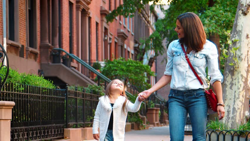 Mother with red handbag walking in the street with daughter