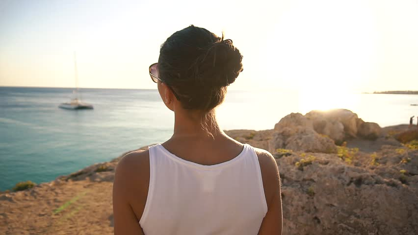 Pretty young brunette girl on the rocks opposite the sea at sunny day in Cyprus