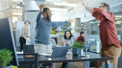 Busy Corporate Office, Man Working on a Laptop Signs Important Contract and Jumps in Celebration, Gives High-Five to His Coworkers. Everybody is Happy. Shot on RED EPIC-W 8K Helium Cinema Camera.