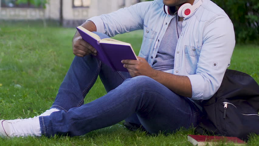 Multiethnic man sitting on grass reading book, recreational activity, bookworm