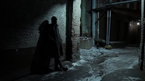 4k Middle age man standing at the wall at cold night getaway and waiting for someone at winter city