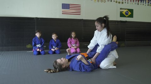 Teenage girls showing Jiu-jitsu moves for children