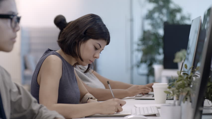 Multi-ethnic employees working at desks in office: concentrated young woman writing down in organizer and typing on computer