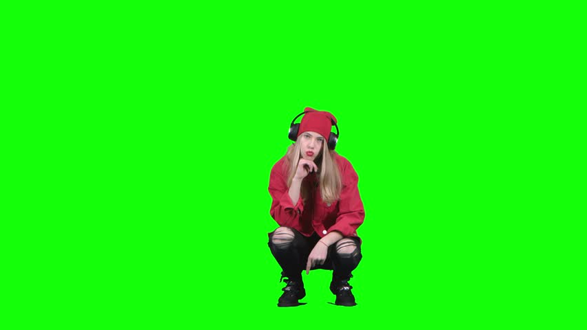 Teen girl sitting on her haunches and listening to music on headphones. Green screen