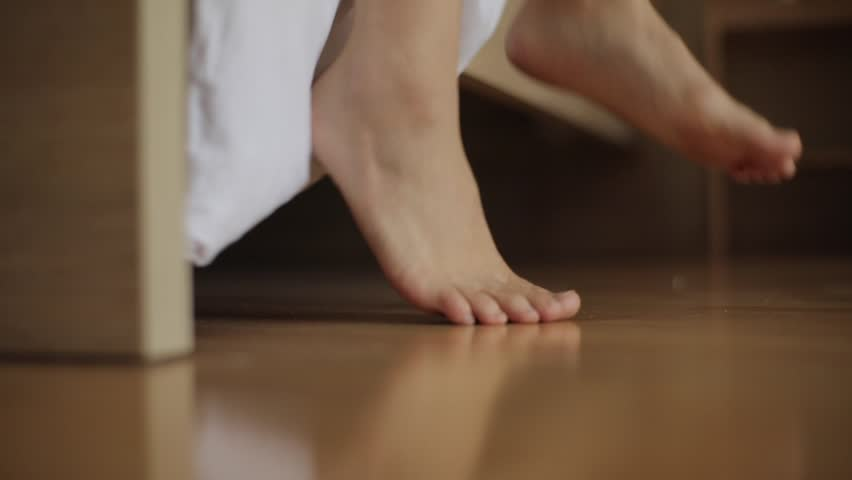 Morning get up from bed slow motion. Female feet step on toes to floor close up. Woman wakes up on wrong side of bed in bedroom with white blanket corner down. Hangover insomnia flatfoot late to work | Shutterstock HD Video #1007078590