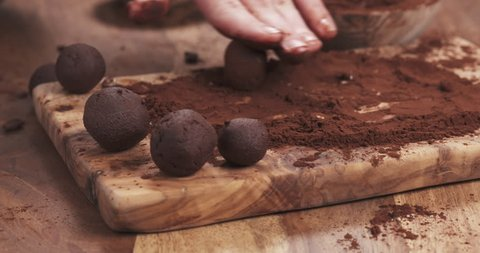 Slow motion handheld shot put truffles in cocoa powder on board