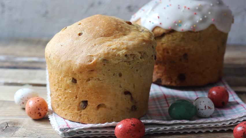 Making sweet bread traditional easter celebration cake panettone or Russian kulich glazed with icing and raisins on vintage ooden table