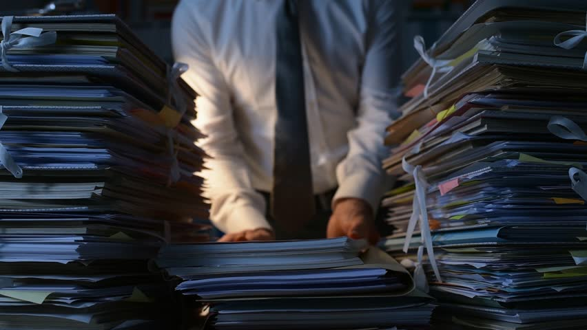 Office clerk stacking paperwork and files on the desk late at night, work overload and bureaucracy concept | Shutterstock HD Video #1007116480