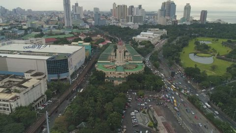 AERIAL: Cinematic Establishing Aerial Shot of the Beautiful Decades old Manila City Hall of Manila, Philippines. Coffin Shape with three-face clock and the largest clock tower of the Philippines