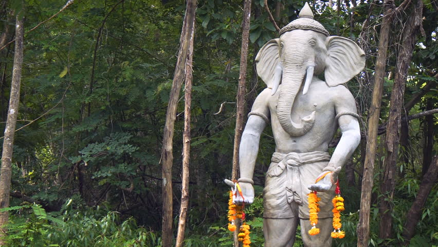 Sculpted image of the Hindu god. Ganesha. outside an abandoned temple in a rainforest wilderness area in Thailand. FullHD 1080p video