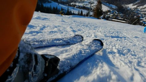 Man feet skiing downhill. Legs view of young man on ski slope. Skier having fun on snow mountain. Winter sport, travel and vacation. Recreation, leisure outdoor activity. Alpine ski resort.