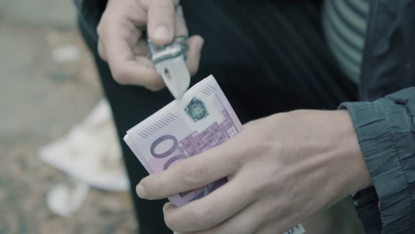 A man holding a knife and money. Preparing the attempt on the life of. Doubt and conscience. Close-up money