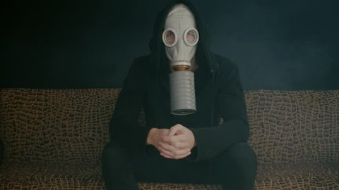 Man in a gas mask sitting in smoke in a dark room. Stalker in the post-apocalyptic world