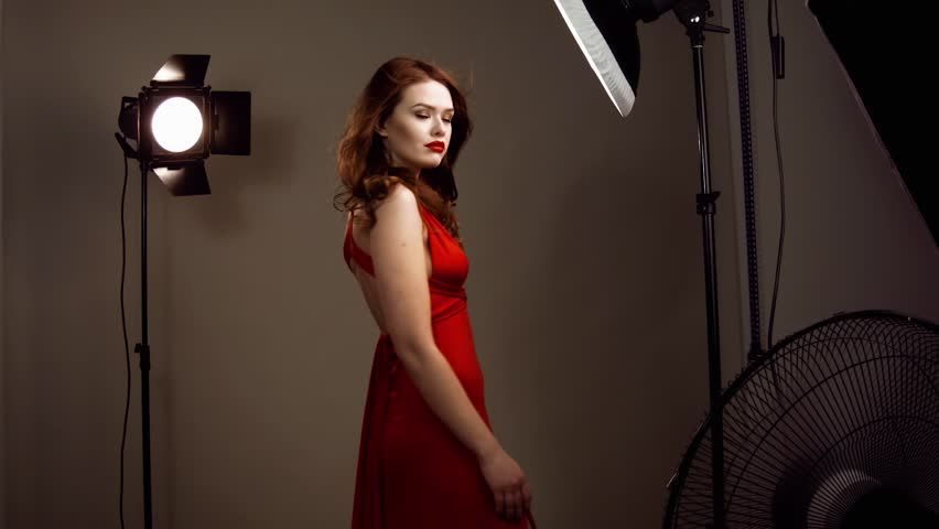 Beautiful female model posing at studio in the light flashes. Model posing at the photo studio softboxes on the background. Hair develops in wind. Fashionable woman with red lips and red dress.
