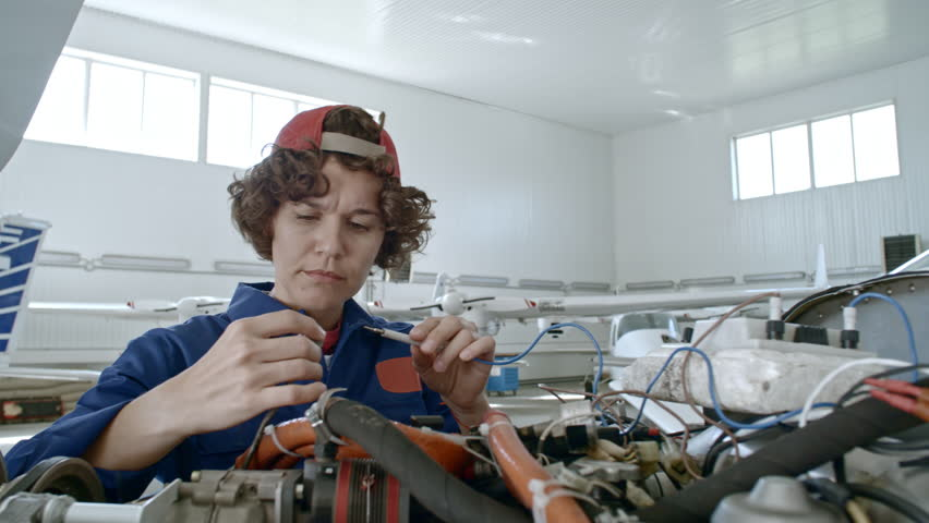 Professional female maintenance mechanic attaching testing device to airplane engine in hangar