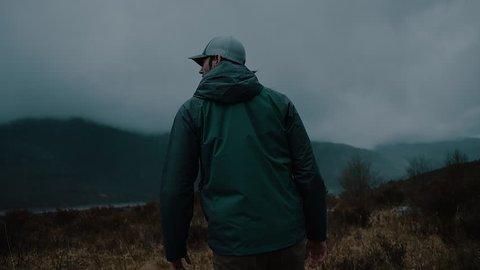 Man Walking in a Dark Misty Mountain Field